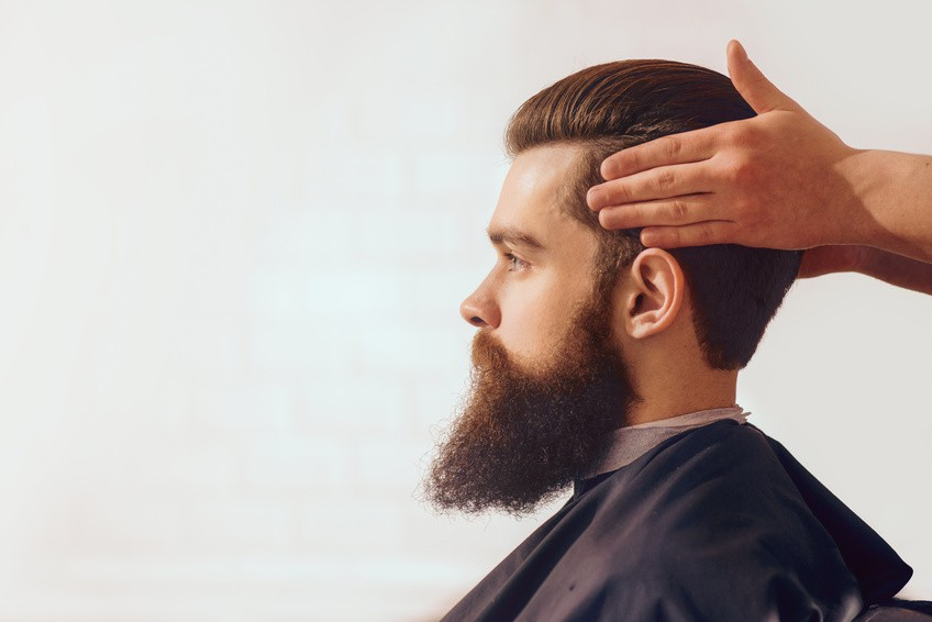 Confident look. Bearded handsome man sitting in the barbershop while professional barber styling his hair